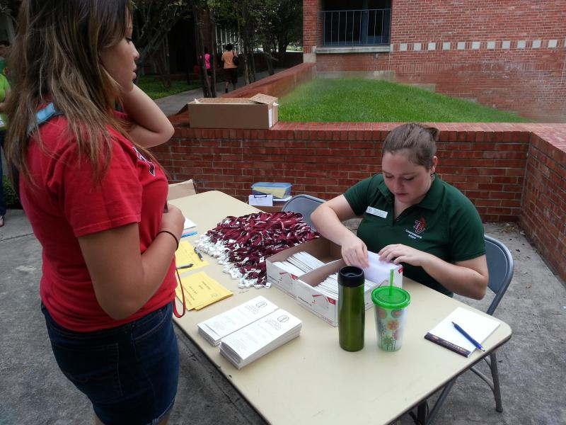 Alecia Jarrett, Head Student Assistant at Trinity University, distributes room keys to Camp GenTX students on Monday.