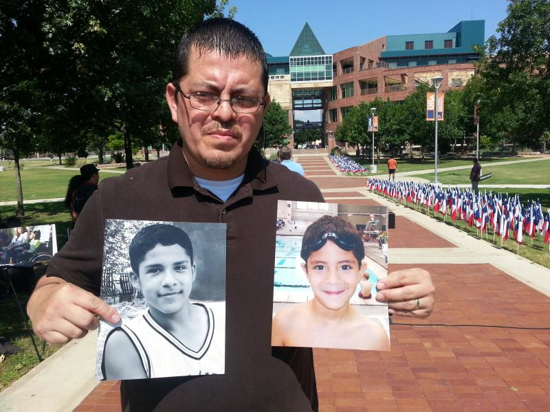 Edward Jimenez holds pictures of his son, Matthew (on the right) and neighbor, 14-year-old Ricky.