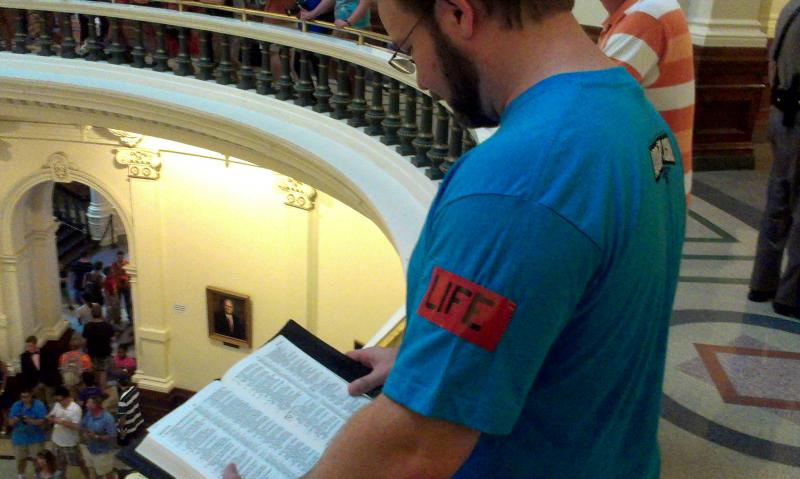 A pro-life supporter reads the Bible at the state capitol as lawmakers engaged in heated debate over the new abortion clinic restrictions in July 2013.