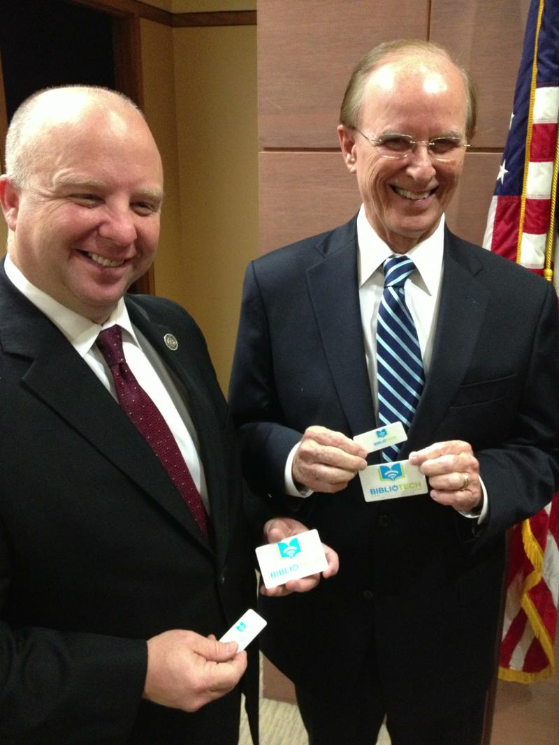 Commissioner Kevin Wolff and Bexar County Judge Nelson Wolff pose while holding their library cards.