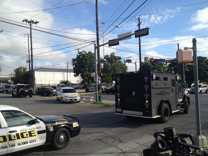 A SWAT vehicle approches the Super 8 Motel (white building) to negotiate with the suspect.