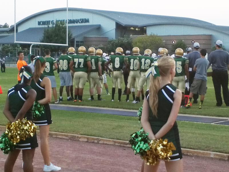 Cole High School cheerleaders and football players under the Friday night lights.