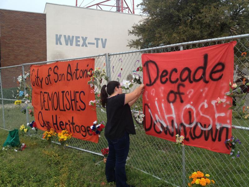 A woman places flowers on the fence erected outside of the Univision TV station