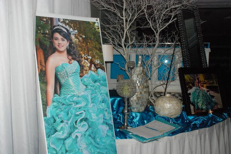 Professional photographs of Julissa Canal greet guests as they enter the hall for her quiceañera.