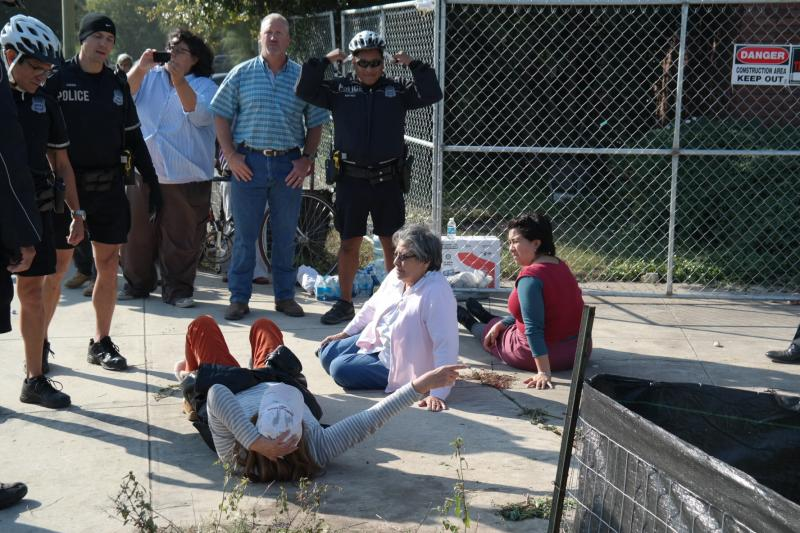 The second group of three people lay on the ground to block a truck and are arrested by police.