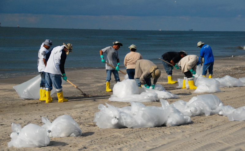 Workers in 2010, cleaning up a beach during Deepwater Horizon event.