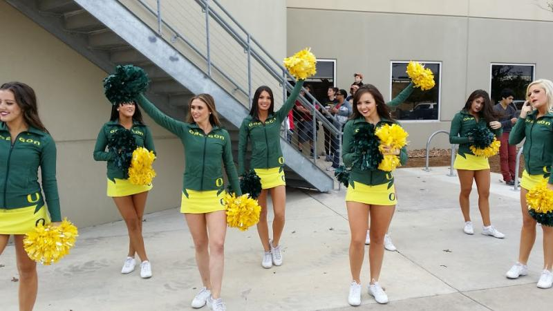 Oregon cheerleaders welcomed dignitaries to the Food Bank Sunday, including the university's president, Michael Gottfredson.