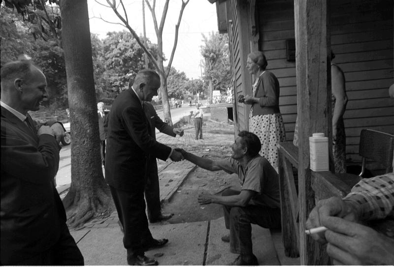 War on Poverty Tour: President Lyndon B. Johnson shakes the hand of one of the residents of Appalachia as Agent Rufus Youngblood (far left) looks on