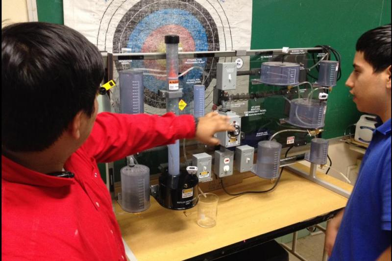 Junior Chris Harrison (left) demonstrates how the model ethanol plant creates the usable fuel.