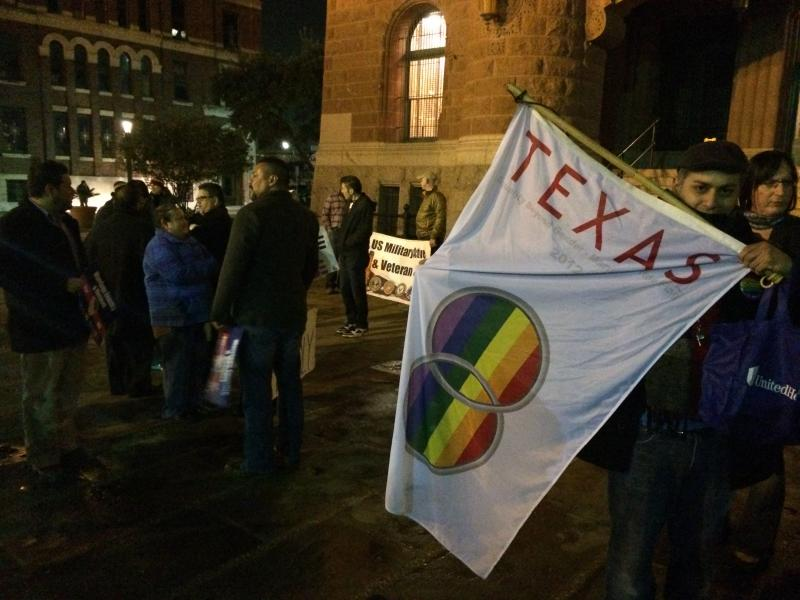 Same-sex marriage activists, including Carlos Soto, holding a flag, gathered in front of the Bexar County Courthouse Wednesday night after the ruling.