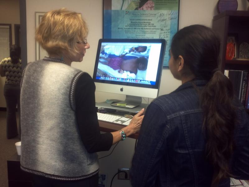 Dr. Ruth Berggren and high school student Nita Tunga study photos of Haiti relief efforts.
