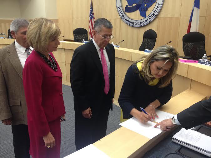 South San Board President Helen Madla signs the contract for newly hired superintendent Abelardo Saavedra (center)