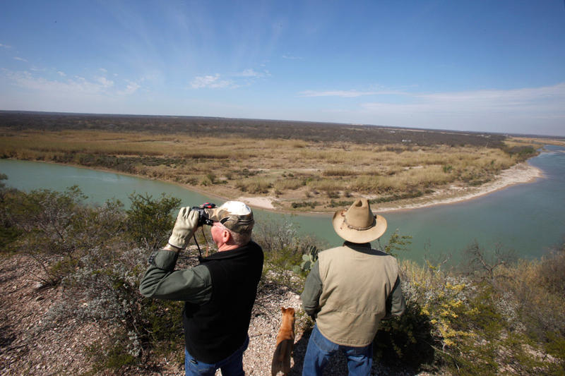 Texas rancher Dob Cunningham, right, stands on the edge of his 800-acre ranch in Quemado, Texas, which touches the Rio Grande. On the other side, Mexico.