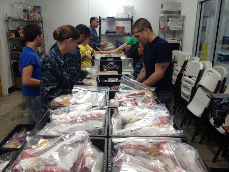 Volunteers with the U.S. Navy seperate and sort peanut butter and jelly sandwiches for first day of distribution.