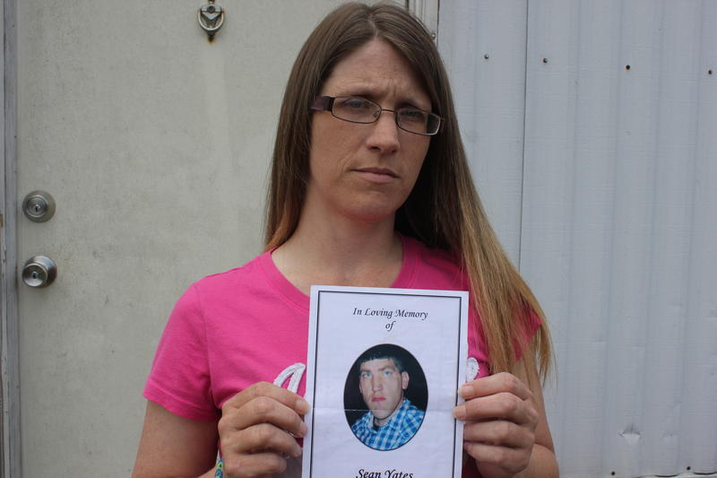 Ashley Yates holding up a photo of her older brother Sean Yates who died after running away from the Corpus Christi State Supported Living Center.