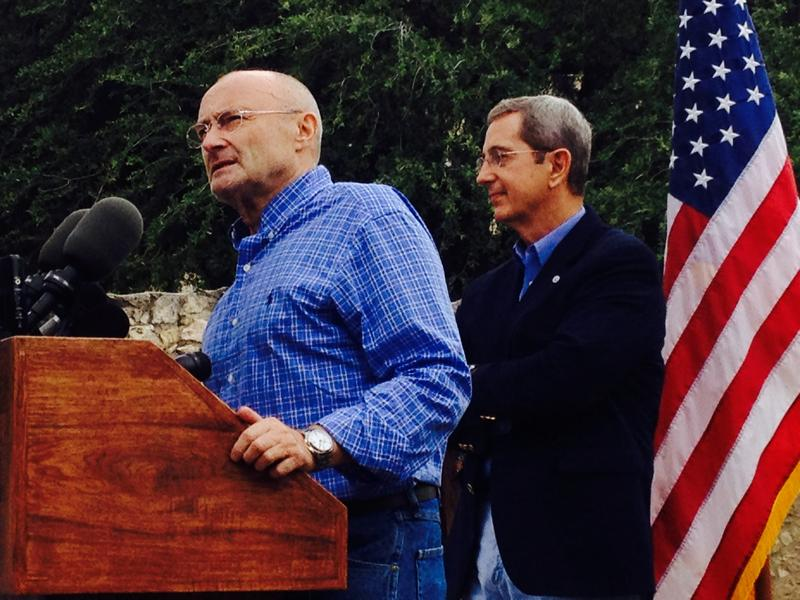 Phil Collins at the microphone, with Land Commissioner Jerry Patterson.
