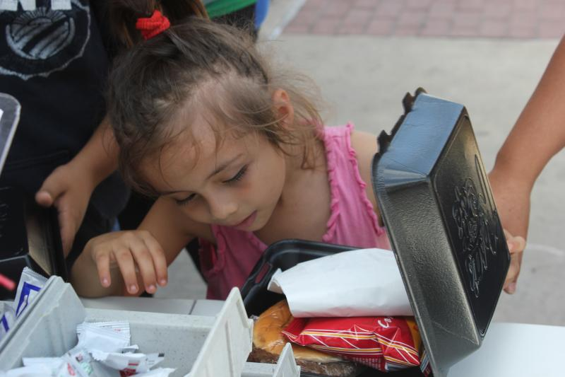 Outside the McAllen bus station a little girl, a refugee from El Salvador, inspects the hamburger she was given by the Salvation Army disaster relief truck.