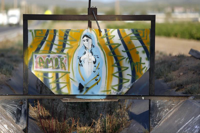 A painting of Our Lady of Guadalupe decorates a gate on an irrigation ditch in New Mexico.