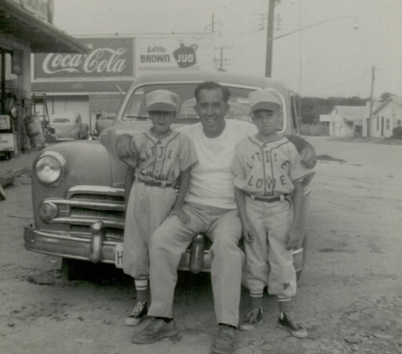 Everyday life from the barrios of San Antonio.  These kids grew up playing on the diamond. Coach Fred Lozano with his son Noey Lozano on the right.  Charlie Calderon is the other Little Flowers player in this picture