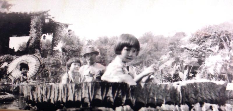 Young Jingu girls sitting on huge lily pads. Groundskeeper Hugo Gerhardt looking on.
