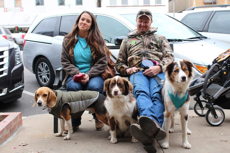 A couple stops for a break with their three dogs along Main Street in Fredericksburg.