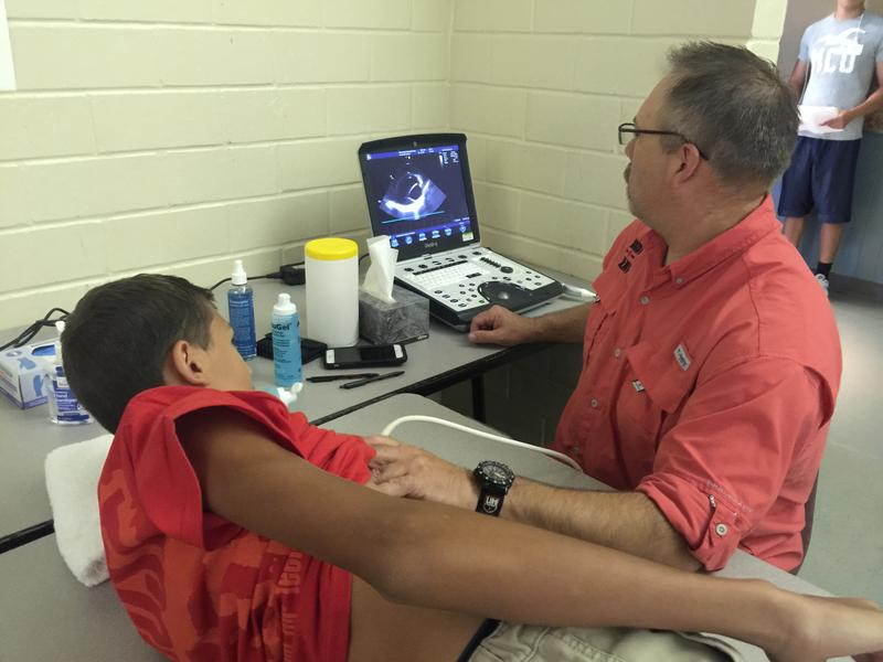 A volunteer cardiac sonographer conducts an echocardiogram