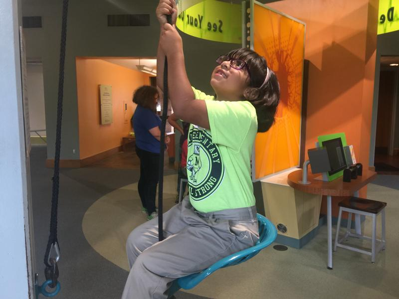 Children try to pull their own weight in the Body Adventure exhibit.
