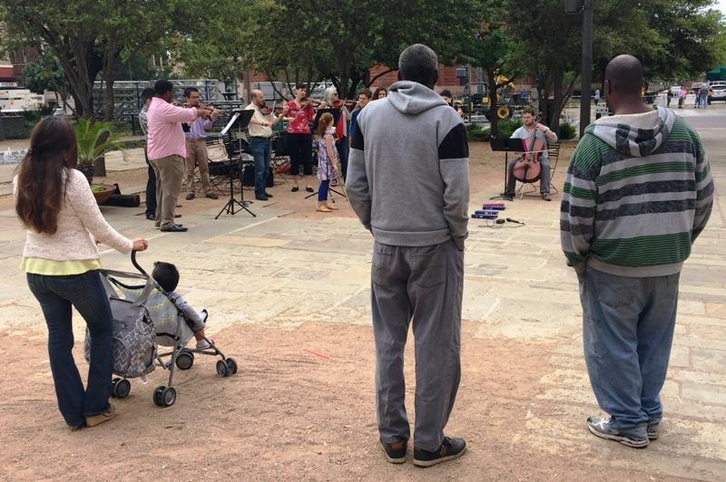 bystanders watch musicians at Main Plaza
