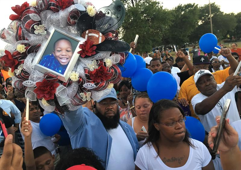 4-year-old De-Earlvion Whitley was killed in a drive-by shooting in July. His mother, Cyntwanisha Whitley, is pictured in white at the vigil.