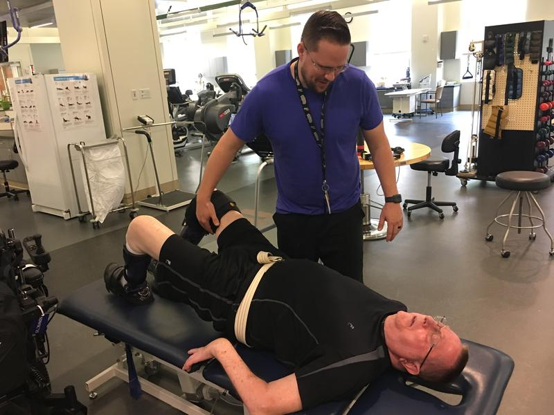 Physical therapist Dillon Bomer works with veteran William Geralds in the gym at the Polytrauma Rehabilitation Center in San Antonio.