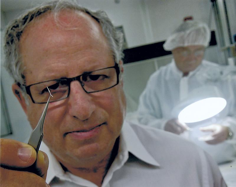 Leonard Pinchuk, MD, holds up a microshunt designed to help prevent blindness in people with glaucoma.