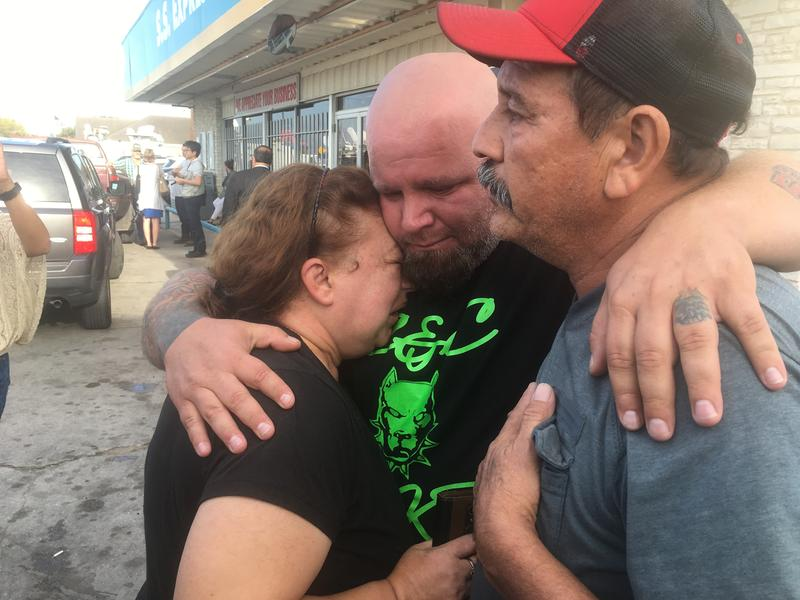 Terri Smith, far left, and Lorenzo Flores, far right, receive a hug from one of their Sutherland Springs neighbors.