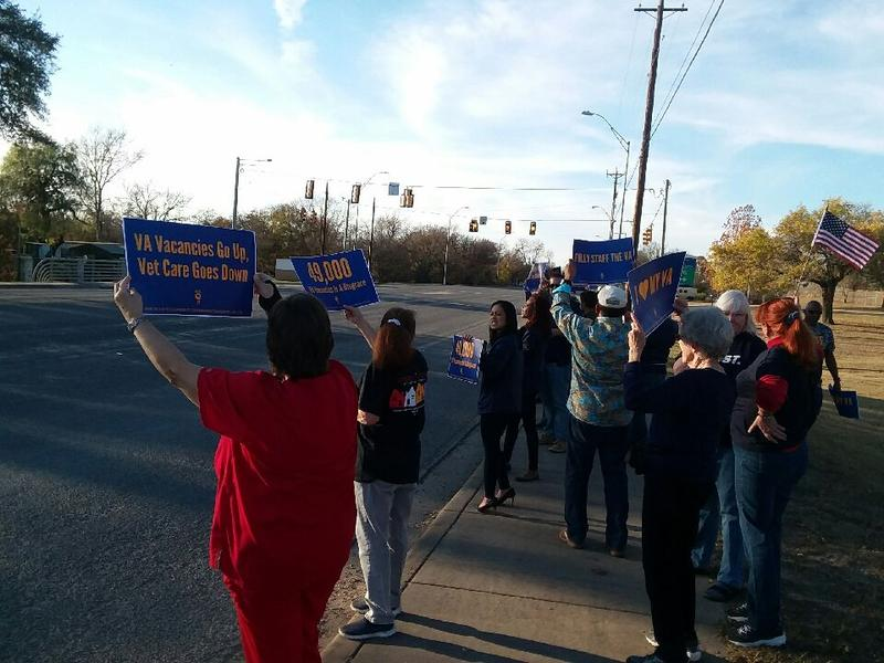 Members of the community and the American Federation of Government Employees display signs on the sidewalk in front of Kerrville VA Medical Center.