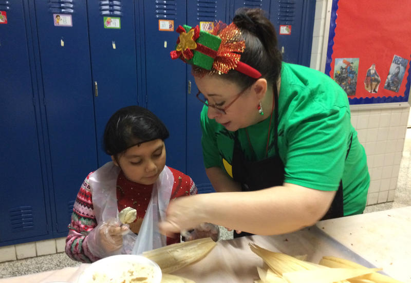 Bilingual teacher Yvonne Velasco, right, helps fourth-grader Nimzy Ballinas spread masa on a corn husk to make a tamale at De Zavala Elementary Dec. 21, 2017.