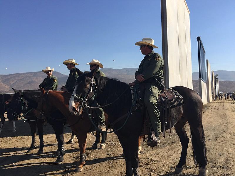 Border Patrol agents ride past border wall prototypes, Oct. 26, 2017.