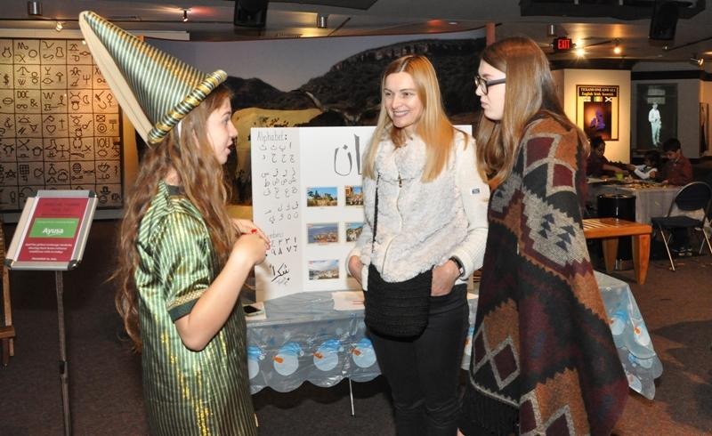An AYUSA student in her native attire talks with guests about her home country of Lebanon