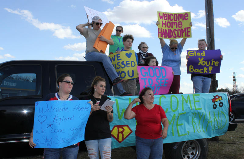 Melissa Salinas and her family and friends decorated a truck to welcome Ryland Ward home from the hospital. Terrie Smith, right, and other neighbors peer down the road in anticipation of his arrival Jan. 11.
