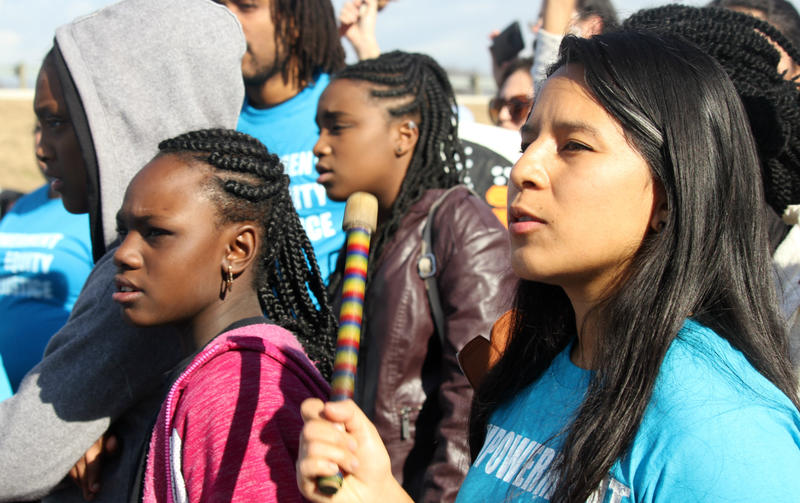 Excy Guardado keeps the beat witha handheld drum as girls from the Martinez Street Women's Center youth development program sing at the MLK Day march Jan. 15, 2018.