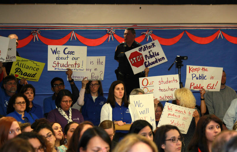 Members of San Antonio Alliance, which represents SAISD teachers, hold up signs protesting Democracy Prep's application to run Stewart Elementary during the Jan. 22, 2018  trustee meeting.