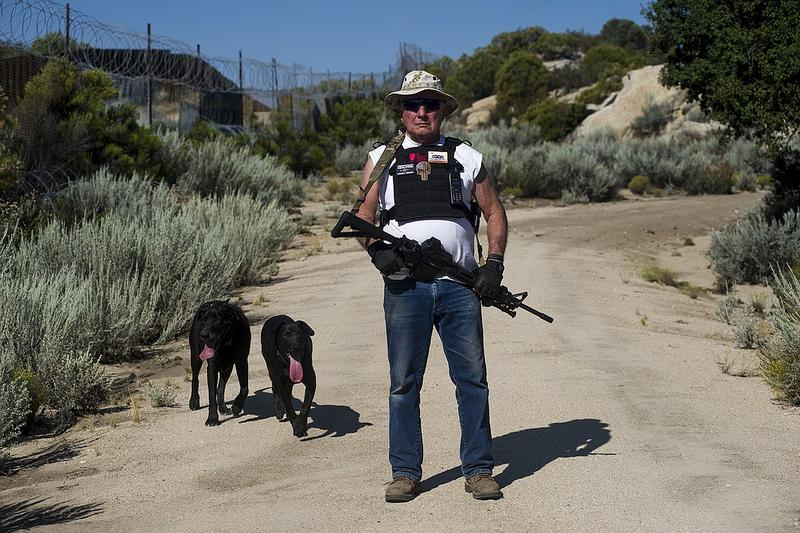 Bob Maupin, 78, poses on Aug. 30, 2017, for a portrait with his dogs Shadow and Inky while patrolling his ranch that borders Mexico. Maupin erected his own 10-foot-high fence, including razor wire at the top, which took him five years to build.