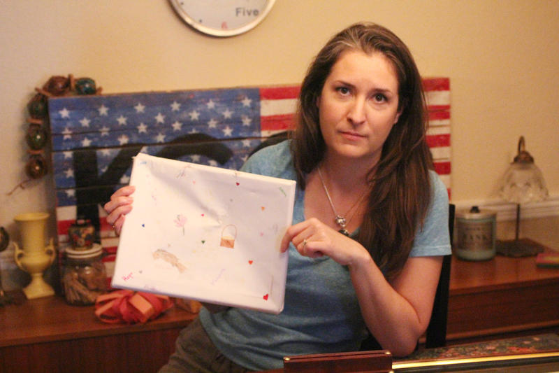 Sarah Taranto holds a piece of artwork made by her daughter. It was damaged during her permanent change of station move, along with other items.