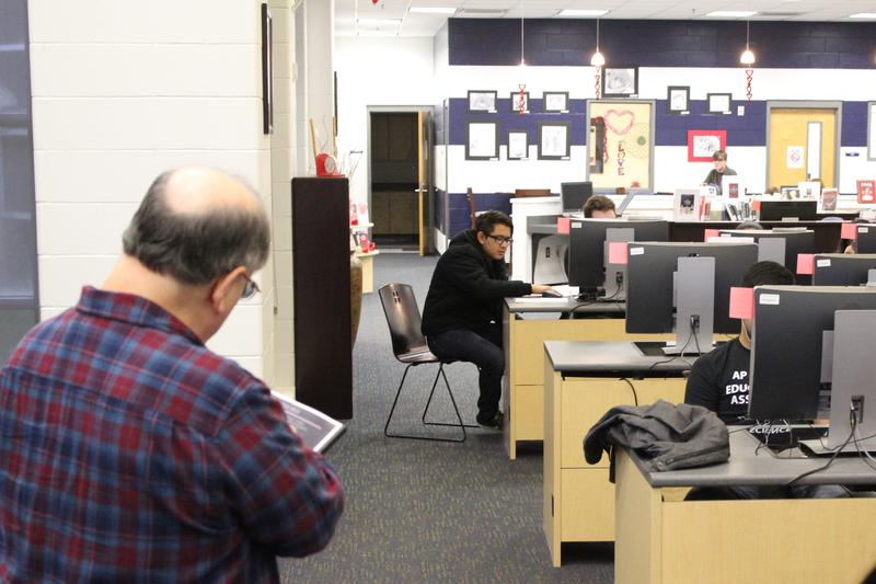 Teacher Barry Glasser works with his students in the library at Southwest Early College H.S.