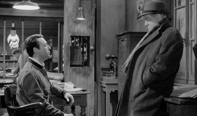 Maigret (Jean Gabin) listens to a newspaper man (Jean-Pierre Granval) in MAIGRET AND THE ST. FIACRE CASE.
