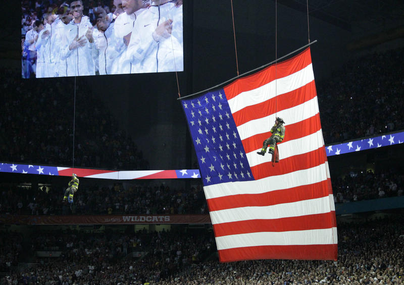 A flag was raised by members serving at Joint Base San Antonio while firefighters descended by ropes from the ceiling during the pregame show.
