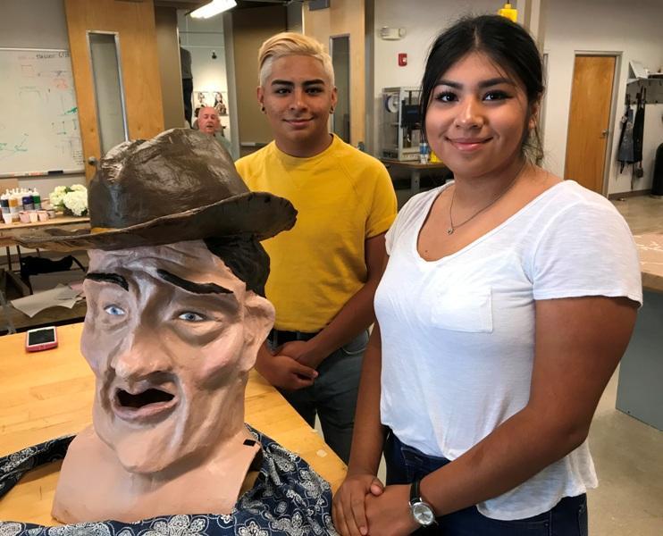 Students Malachi Mercado and Maria Monsivais show off their creation, a cowboy made of papier-mache.