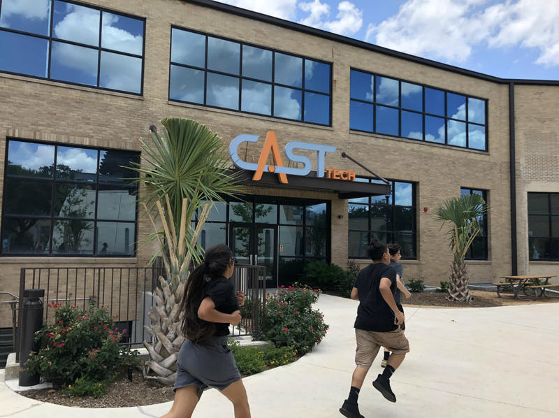Students run past CAST Tech High School, one of San Antonio ISD's new specialized schools in May 2018.