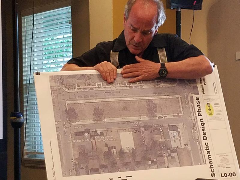 Landscape architect Larry Clark holding a map of the neighborhood. Phillis Wheatley Park lies just above center.
