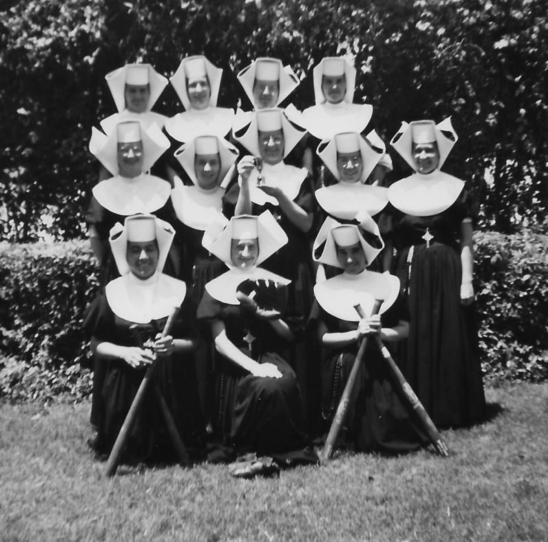 Another activity in which the sisters participated was softball. Their habit skirts were pinned up, sleeves rolled up past the elbows, and veils pinned back with a clothespin. Competition was stiff. This picture features the happy championship team.