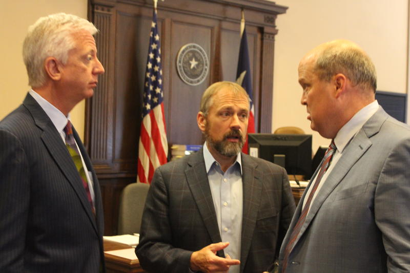 Secure San Antonio's Future Campaign Manager Christian Archer (center) talks with philantropist Gordan Hartman and attorney Mikal Watts in Judge Stryker's courtroom.
