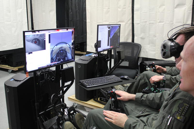 Airman 1st Class Jack Pepper attempts a maneuver on a simulator while Lt. Col. Paul Vicars looks on. At the top left of Pepper's screen is an eye movement tracker that measures cognitive load.